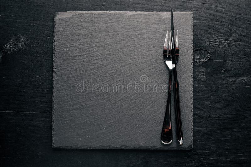 Black stone board with cutlery. On a wooden background. Top review. Free space stock photography