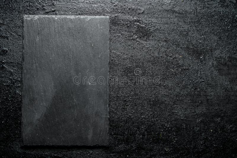 Black stone Board. On black rustic background stock photo