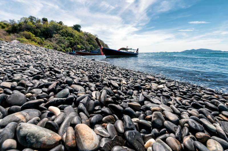 Black stone island with wooden boat on coastline in tropical sea. At Koh Hin Ngam stock photography