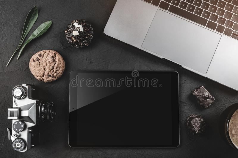 On a black stone table is a laptop for work, a photo camera, a graphic tablet and sweets. Top view, flat lay royalty free stock photography