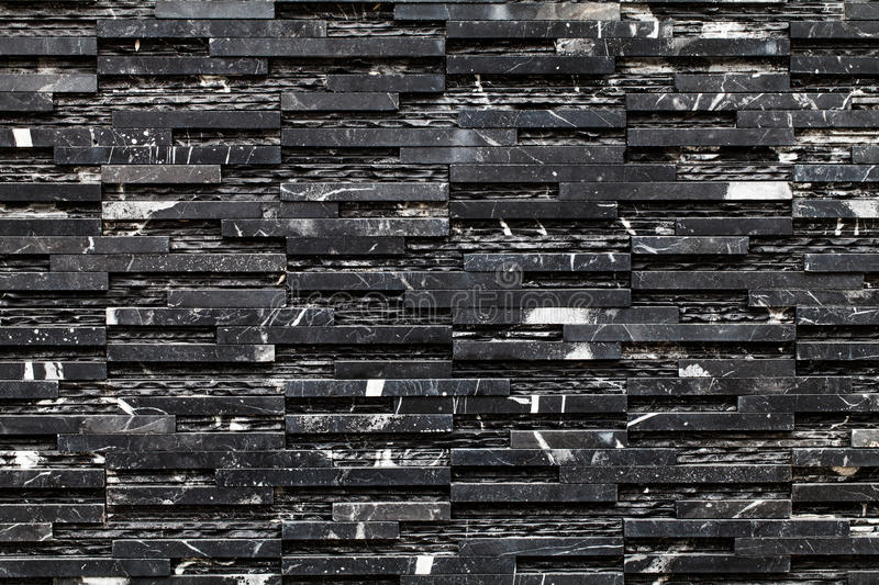 A black stone wall. Closeup of a black stone wall stock images