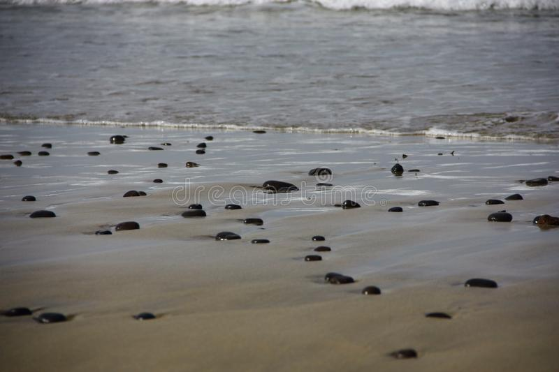 Black stones on the beach royalty free stock photography