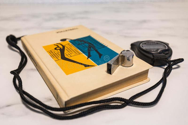 Black stop watch, training book and whistle on a marble plate royalty free stock images