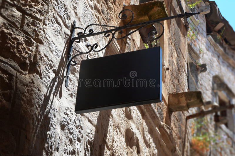 Black store sign mockup in old city street.  royalty free stock images