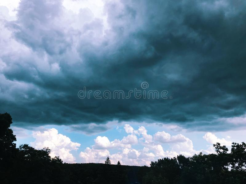 Black storm clouds over the sky. With blue sky and white clouds on the horizon in summer new england Connecticut United States stock photos