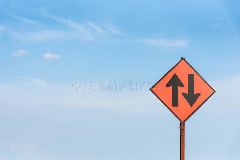 Black straight traffic and go back arrow sign under the blue sky stock photos