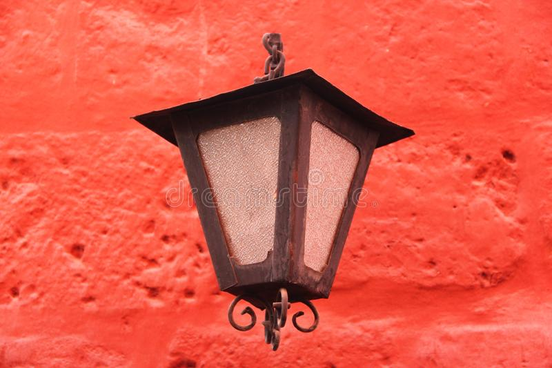 A black street lantern against a red wall. A black street lantern decorates a red wall at the monastery of Santa Catalina in Arequipa, Peru stock photos