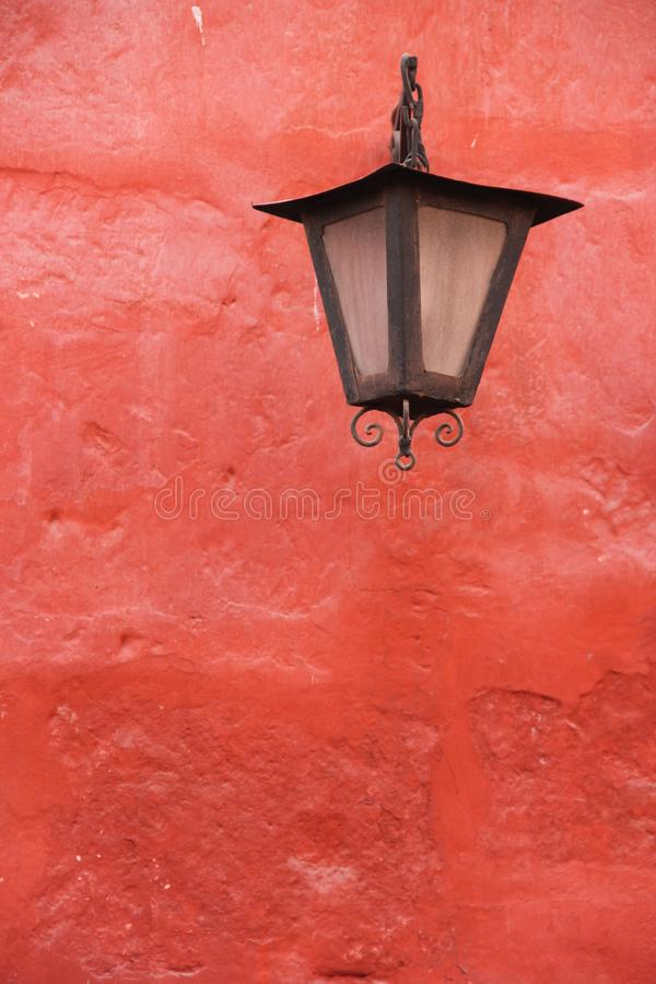 A black street lantern against a red wall. A black street lantern decorates a red wall at the monastery of Santa Catalina in Arequipa, Peru stock photo