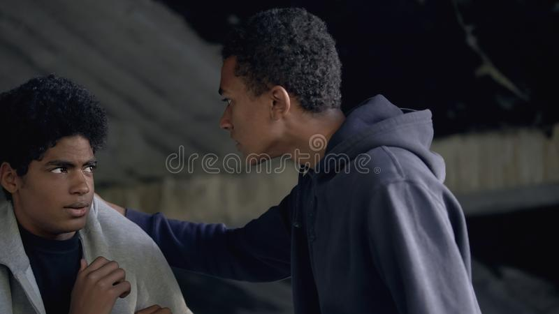 Black student bullying frightened male teenager, communication conflict, abuse. Stock photo royalty free stock photography
