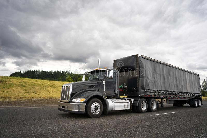 Black stylish big rig semi truck for local haul transporting car. Black stylish big rig American popular professional semi truck for local haul delivery royalty free stock photography