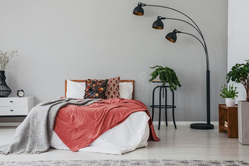 Black stylish lamp in elegant bedroom interior with comfortable double bed, plants, and bedside table. Real photo with copy space on the wall stock photography