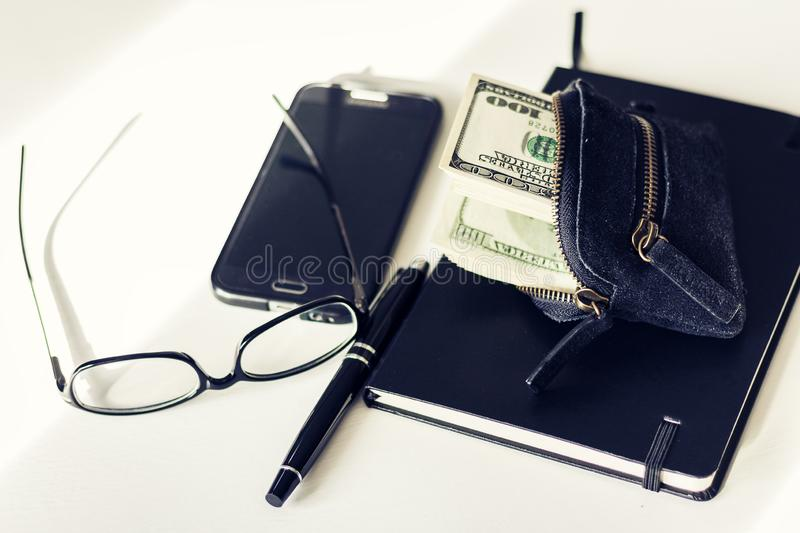 Black suede purse with dollars sticking out of it notebook, smartphone, glasses and pen on white background stock photography