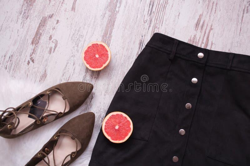 Black suede skirt, brown suede shoes, cut grapefruit halves. Wooden background. Fashion concept. top view stock photos