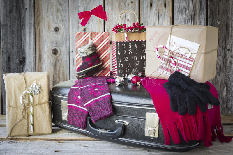 Black suitcase with Christmas gifts sitting on top. stock photo