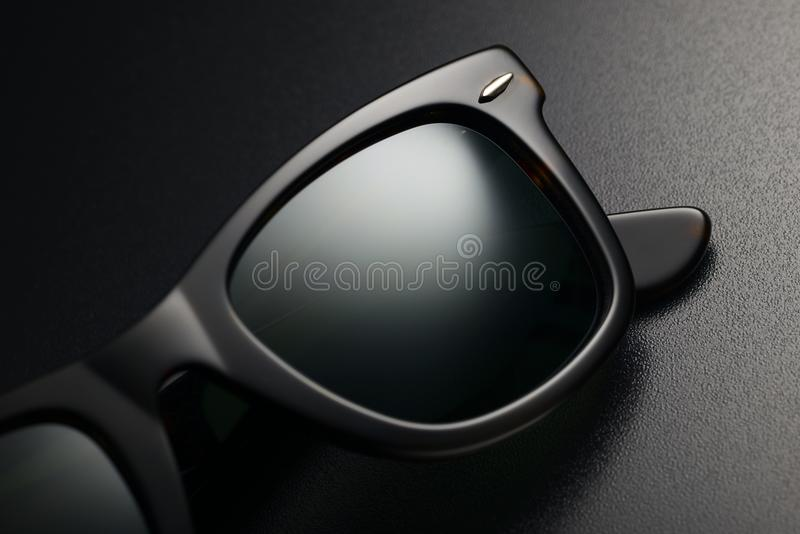 Black sunglasses isolated. Detail of black plastic classic sunglasses on the black background royalty free stock images