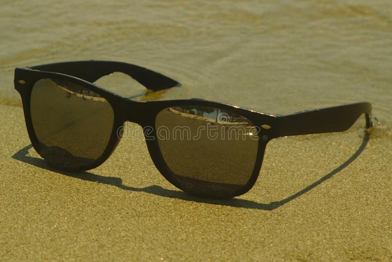 Sunglasses in waves at sandy beach stock image