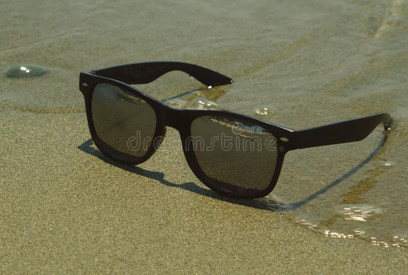 Sunglasses in waves at sandy beach royalty free stock photo