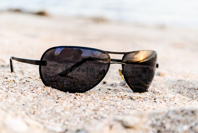 Sunglasses on sand with reflection of sunset at sea and photographer stock image