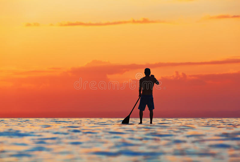 Download Black Sunset Silhouette Of Paddle Boarder Standing On SUP Stock Photo - Image: 93432504