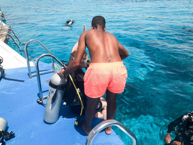 A black, swarthy, Arab athletic athletic man helping divers in black scuba diving suits with oxygen bottles sinks under the transp royalty free stock photography