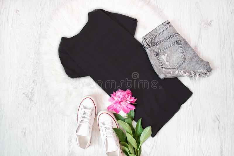 Black t-shirt, gray shorts, white sneakers and pink peony. Fashionable concept.  stock photo
