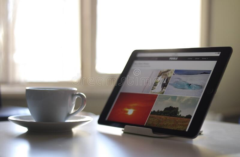 Black Tablet Computer Near a White Ceramic Teacup royalty free stock photos