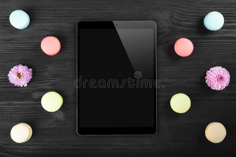 Black tablet pc looking similar to ipad and colorful macarons on old dark wood background stock images