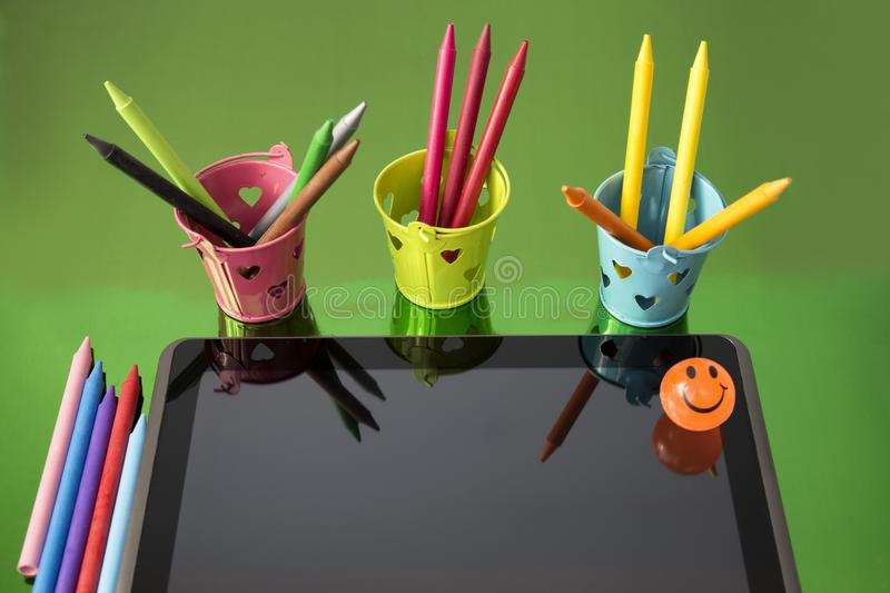 Black tablet surrounded by multicolored pencils with originals containers on bright green background. Top view of black mobile device and multicolored pencils stock images