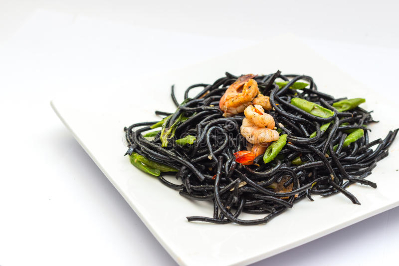 Black tagliatelle with shrumps, mussel and squid. Black tagliatelle (pasta made with cuttlefish ink) with shrumps, mussel and squid royalty free stock images