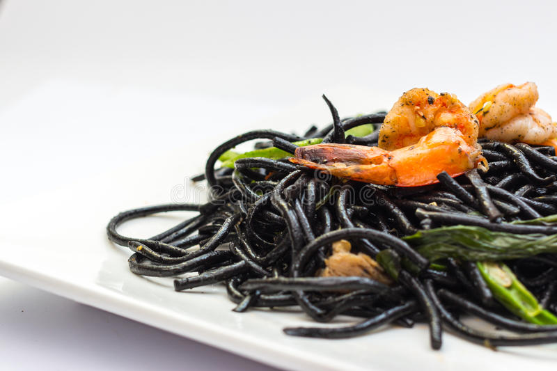 Black tagliatelle with shrumps, mussel and squid. Black tagliatelle (pasta made with cuttlefish ink) with shrumps, mussel and squid stock photos