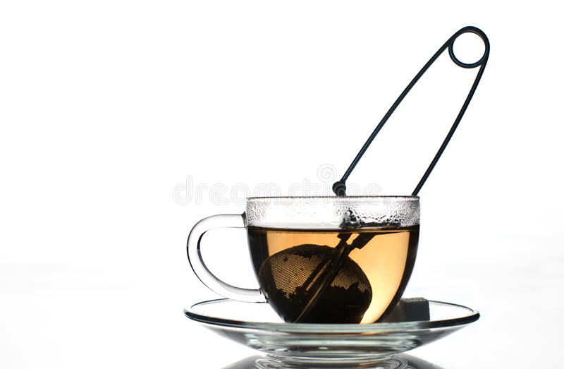 Black tea. Brewing black tea in glass cup with strainer royalty free stock images