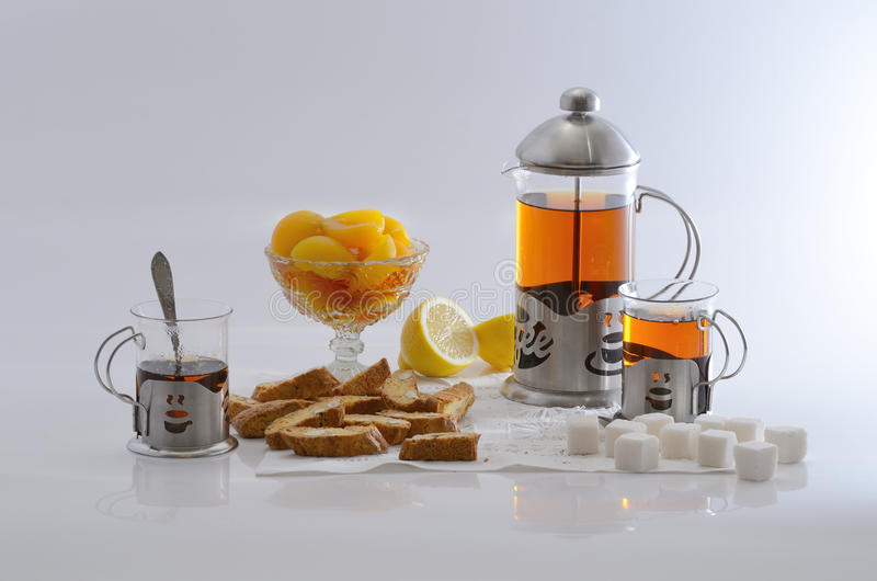 Black tea with apricot halves. Lemon, sugar and biscuits royalty free stock photo