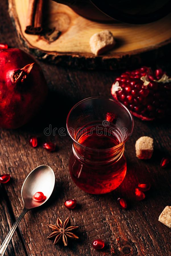 Black tea in arabic tea glass with fresh pomegranate and some spices stock photo