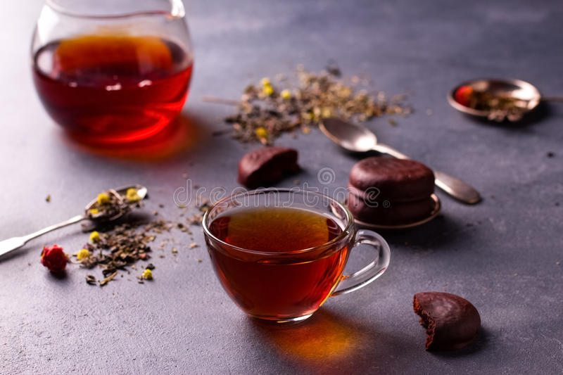 Black tea in a cup. Black tea in a transparent glass cup on grey stone table with glazed chocolate cookies and tea leafs royalty free stock images