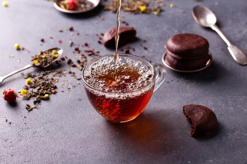 Black tea in a cup. Black tea in a transparent glass cup on grey stone table with glazed chocolate cookies and tea leafs stock photos