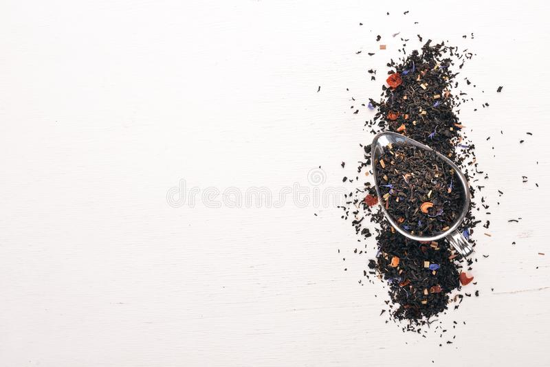 Black tea with flower petals of cornflower and dry berries. On a wooden background. stock photography