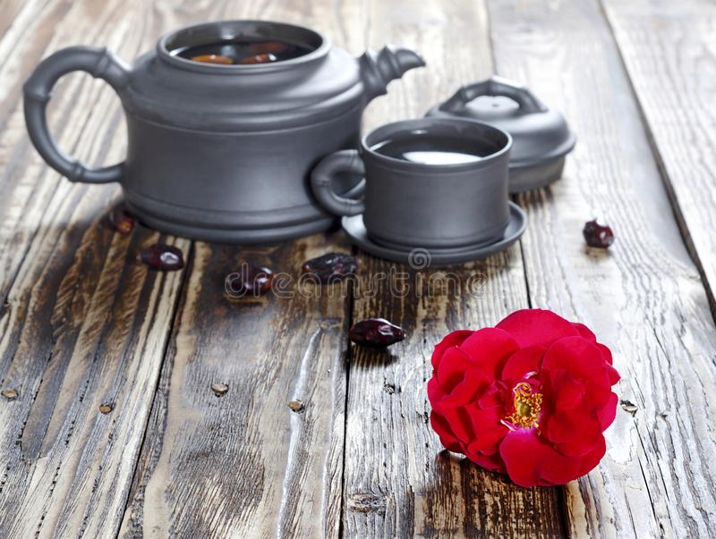 Black tea flower set. Oriental tea set of teapot and mugs of black ceramic with tea fruits and rose hip flowers on a brown wooden table in the countryside stock photography