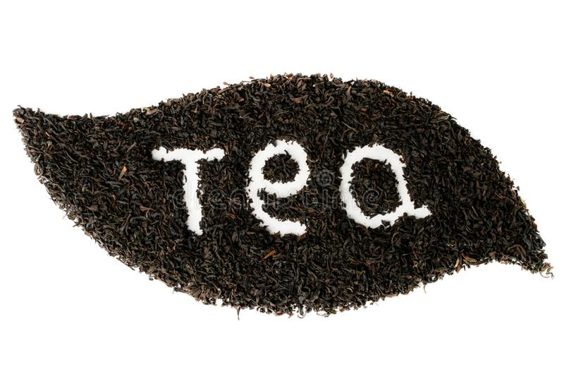 Black tea leaves lined with leaf shape on white background isolated. stock image