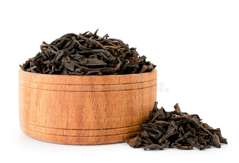 Black tea leaves in a wooden plate close - up on white. Isolated. stock image