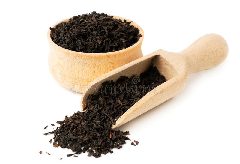 Black tea leaves in wooden plate and spoon on a white stock photography