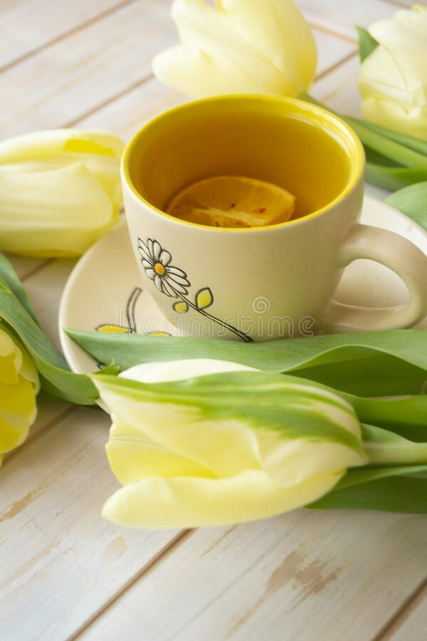 Black tea in the pastel yellow cup and lemon, yellow tulips on the white shabby wooden background. Vertical image stock photos
