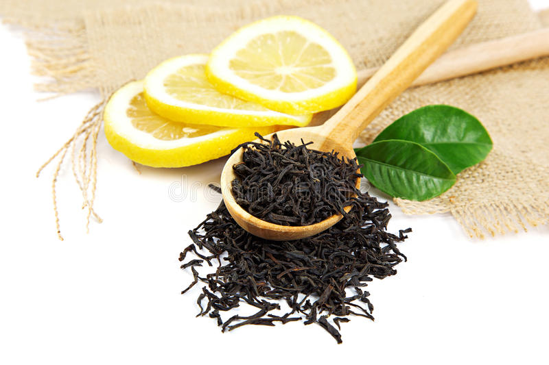 Black tea in wooden spoon and green lemon leaves. stock photo