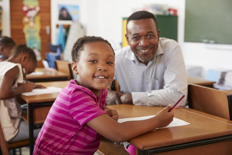 Black teacher and elementary school girl smiling to camera stock photos