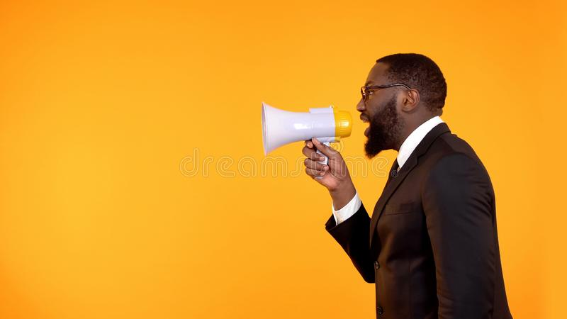 Black team leader making announcement in megaphone, stressful job, deadline royalty free stock photography