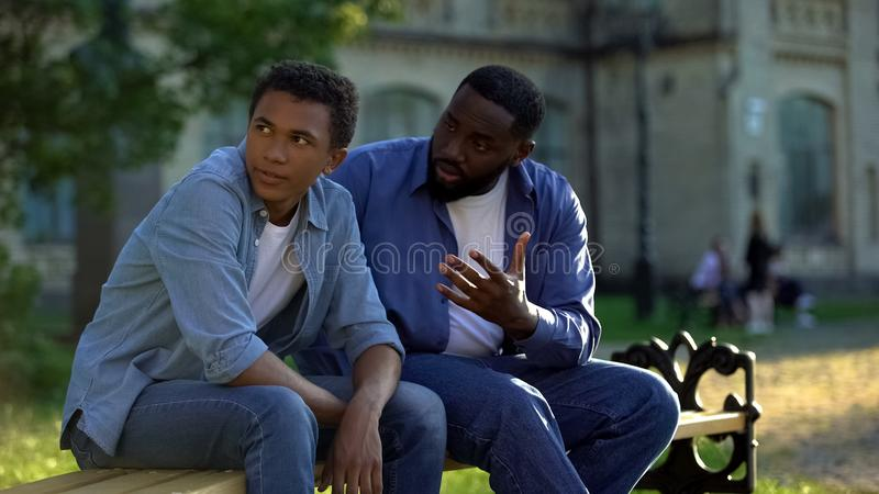 Black teenager male ignoring scolding dad sitting on campus bench, conflict royalty free stock image