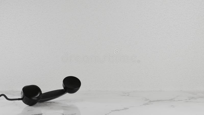 Black telephone ear supine on the black and white marble floor in the room, the background is rough white. Black telephone ear supine on the black and white royalty free stock photo