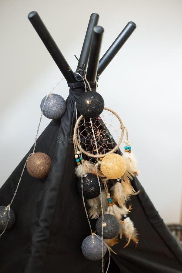 Black textile wigwam with  dream Catcher decor and ball lamp garland. Black textile wigwam with dream Catcher decor and ball lamp garland in room with white stock photos