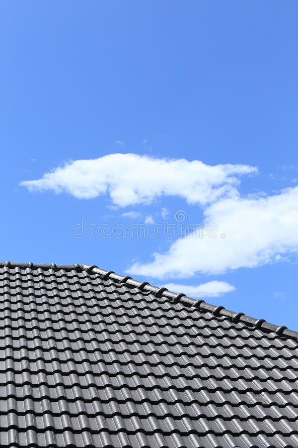 Black tiles roof. On a new house with blue sky royalty free stock photos