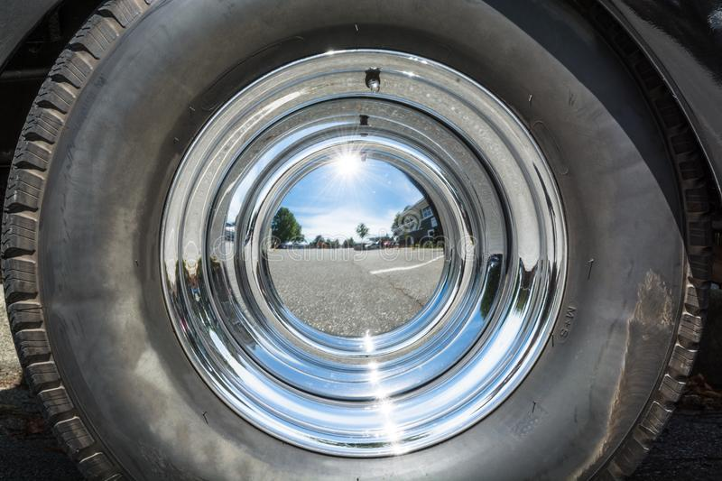 Black tire and chrome mirror cover on the wheel of vintage car. Black tire and chrome mirror cover on the wheel of vintage car royalty free stock photography