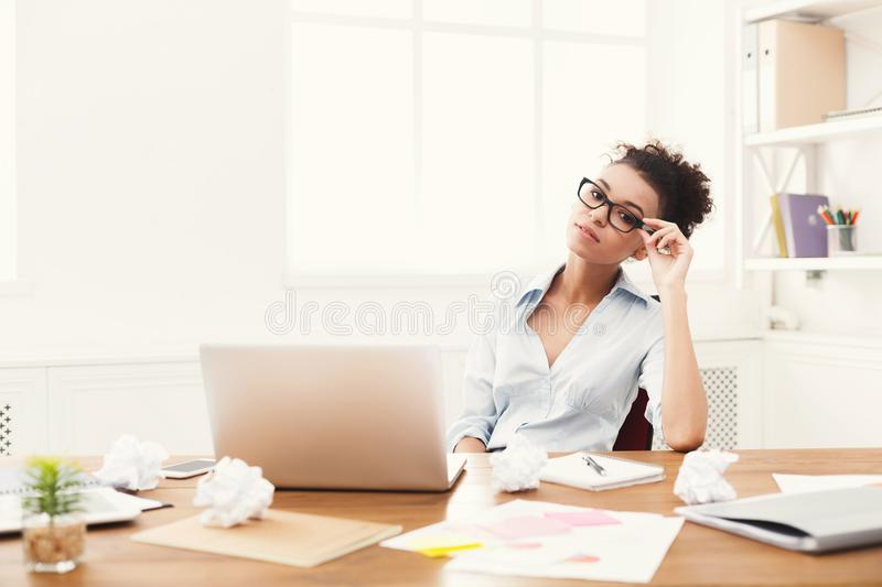 Business woman working on laptop at office. Black tired business woman at office workplace with laptop and lots of crumpled papers. Young girl having break from stock photo